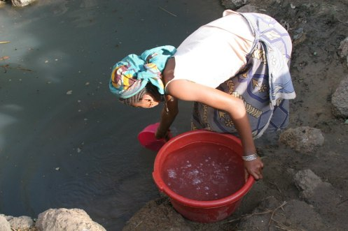 Sa'a Ali collects water from a dirty pond